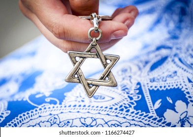 "Young woman's hand holding a Star of David (""Magen David"") key chain. The State of Israel, Holocaust remembrance, Judaism, Zionism concept image. Conversion to Judaism, giyur concept."