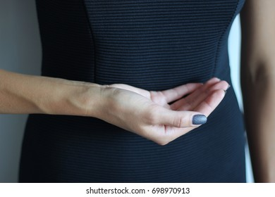 Young woman's hand keeps something. Gesture