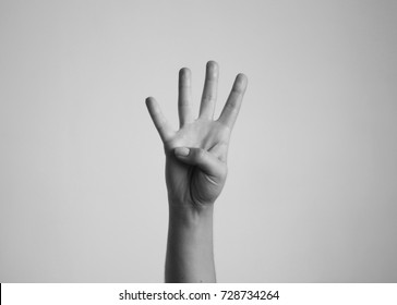 Young woman's hand shows four fingers. Gesture.