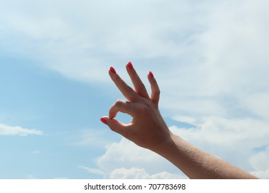 Young woman's hand shows OK Gesture on sky background