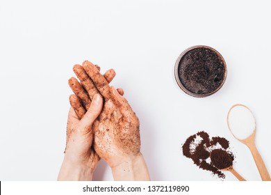Young woman's hands apply massaging moves homemade cosmetic scrub of fresh ground coffee, sugar and coconut oil, top view on white table.