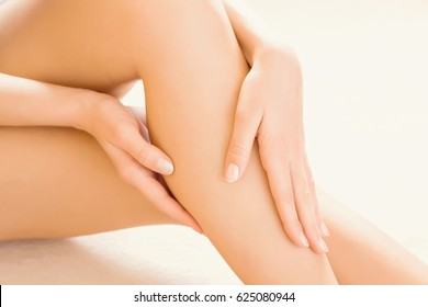 Young woman's hands applying a foot moisturizing cream. Smooth skin.
