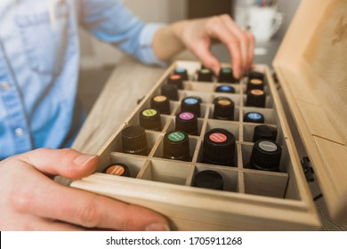 Young woman's hands choosing an essential oil from her essential oil storage box