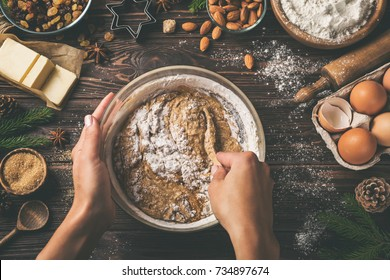 young woman's hands cooking christmas fruit cake. Wooden table with baking ingredients. Top view, toned