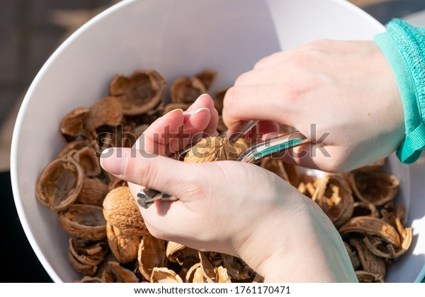 Young woman's hands crack nuts in a bowl