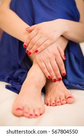 Young woman's hands and feet with red manicure and pedicure. A woman in a blue skirt sitting on a floor