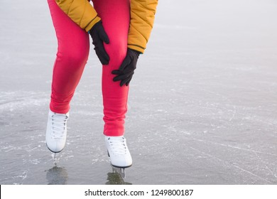 Young woman's hands in gloves touching her knee during ice skating time in winter day. Pain after falling on frozen lake. Sporty problem and solution. Front view.