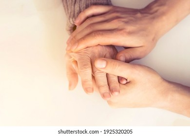 Young woman's hands hold grandmother's hands, an elderly patient. Handshake, caring, trust and support. Medicine, family and healthcare.
