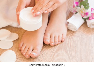 Young woman's hands holding a jar of foot moisturizing cream. Pedicure beauty salon.