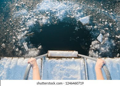 Young woman's hands holding on metallic ladder handles. Ready for swimming in ice hole at lake after sauna in cold day. Care about body health in winter time. Point of view shot. Close up.