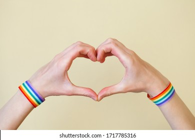 young woman's hands with LGBT colorful rainbow flag wristbands shaped as heart on yellow background, love, gay pride concept, copy space