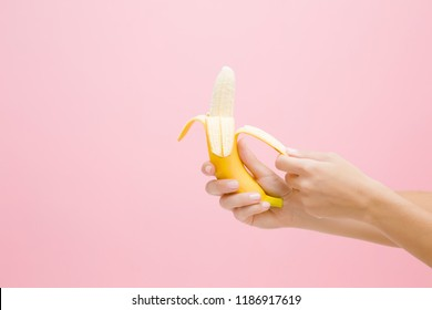 Young woman's hands peeling a beautiful, fresh, yellow banana on pastel pink background. Healthy sweet summer food. Side view.