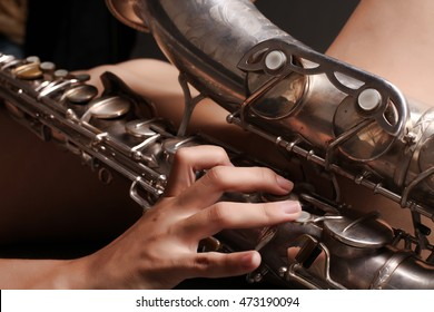 Young woman's hands with saxophone