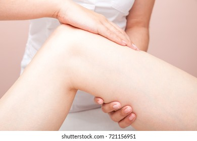 Young woman's leg being manipulated by osteopathic manual therapist or physician