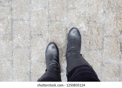 Young woman's legs in black leather boots walking on sidewalk in wet, warm winter day. Pavement covered with slippery ice. Point of view shot. Closeup.