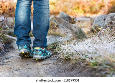 Young womans legs walking through frost iced grass trail path illuminated by morning sunlight at Dolly Sods, West Virginia