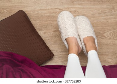 Young woman's legs in the warm, soft, comfortable slippers out of the bed on the wooden floor in the morning after waking up or in the evening before bedtime in the bedroom.
