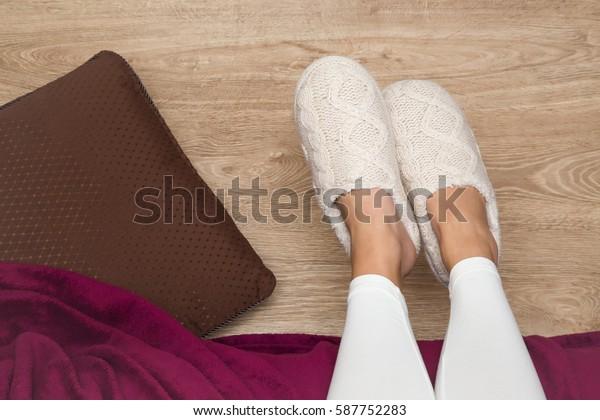 朝起きた後、あるいは寝室で寝る前の夜に、床の上の床の上の暖かく、柔らかく、快適なスリッパを履いた若い女性の脚。