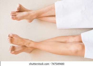 Young woman's and man's legs with white towels. Cares about clean and soft skin after washing. Beauty spa salon concept. Relaxing day. Enjoying life. Empty place for a text.