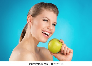 Young woman's portrait with great healthy smile holding green apple. Dental care, teeth protection concept.
