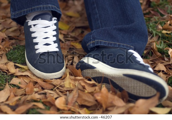 A young woman's shoes resting in the leaves