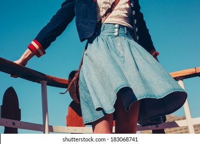 A young woman's skirt is blowing in the wind as she is standing on the deck of a boat cruising down the river