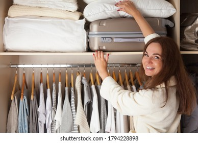 Young woman's wardrobe. Storage and order in the closet on the top shelf. Suitcase and bedding.