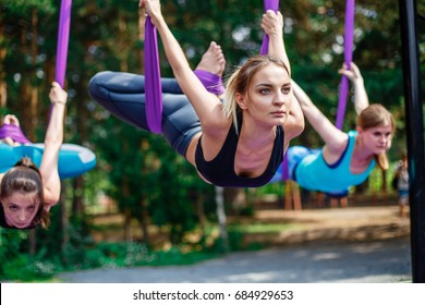 Young women, antigravity yoga exercises with a group of people outdoors. Aero fly fitness trainer.