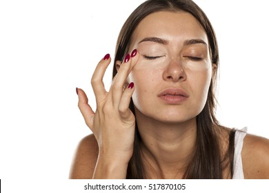 young women applied concealer around the eyes with her finger