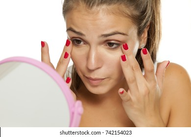 young women applied concealer under the eyes with her fingers