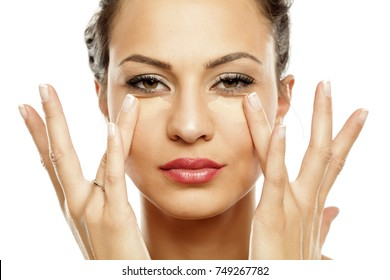 young women applied concealer under the eyes with fingers