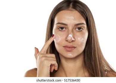 young women apply face cream