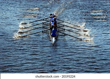 Young women athletes rowing boat