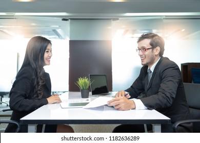 Junge Frauen nehmen an einem Vorstellungsgespräch mit einem Interviewer im modernen Büro teil. Erfolgreiches Bewerbungsgespräch mit Chef und Mitarbeiter-Handshaking.