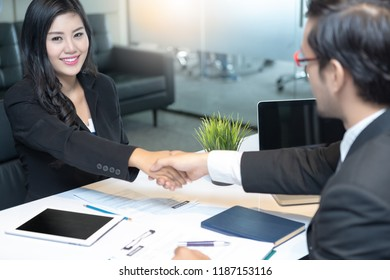 Young women attend a job interview handshake with an interviewer in modern office. Successful job interview with boss and employee handshaking.