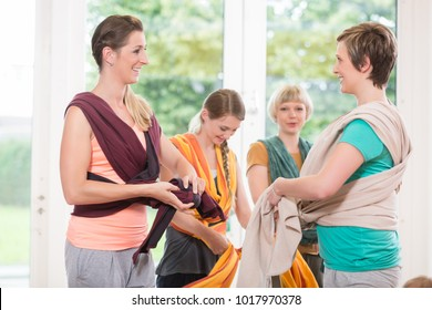Young women at baby course learn how to use baby carriers for carrying children