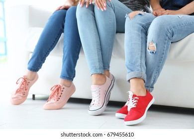 Young women with beautiful legs in jeans and sneakers sitting on sofa
