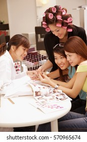 Young women at a beauty salon, getting manicure