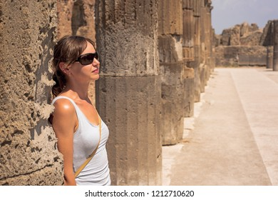Young women behind the ruins of the city of Pompeii. Italy. 2018.08.