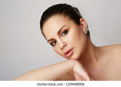 Young women with big brown eyes and dark eyebrows looking over empty gray studio background.Model with light nude make-up.Copy paste text space,close up.Healthcare skin makeup concept