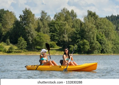 Young women in bikinis kayaking on river summertime