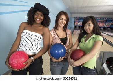 Young women at bowling alley holding balls, portrait