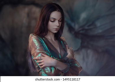 Young women are brunette, spinning and dancing in a dark, gloomy room, the dress fluttering on the fly. Art photo. A woman looks like a sad little mermaid from a fairy tale
