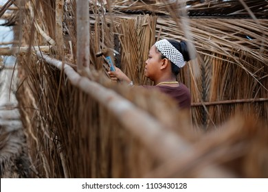 A young women building traditional palm beach hut at Kuala Terengganu, Malaysian on June 21, 2013.