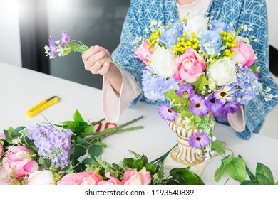 young women business owner florist making or Arranging Artificial flowers vest in her shop, craft and hand made concept.