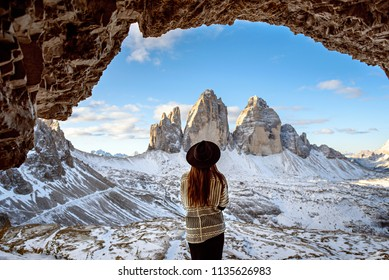 Young women in cave wyth view on Tre Cime di Lavaredo in Dolomites mountains in Italy