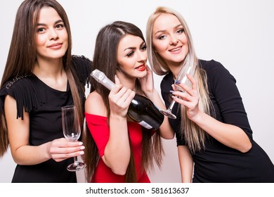 young women celebrating and open champagne on the party over white background