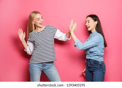 Young women celebrating victory against color background