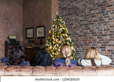 Young women chatting while sitting on the sofa near decorated Christmas tree in the loft. Rear view