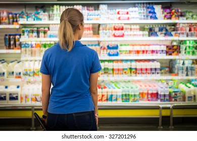 a young women choose to buy on shelf at supermaket